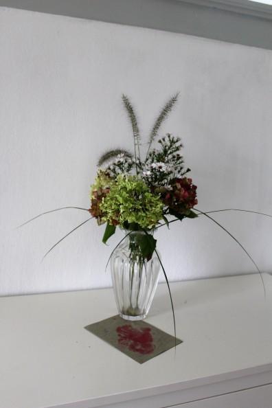 Hortensien und weiße Herbstastern in der Vase