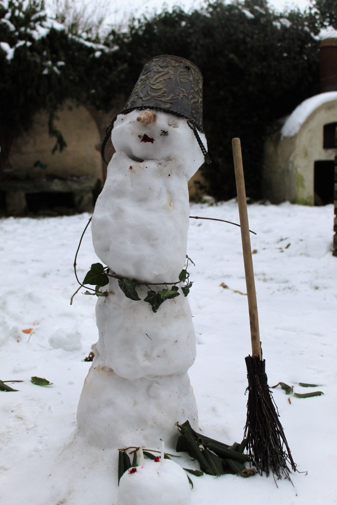 Schneemann im Garten mit Hut und Besen