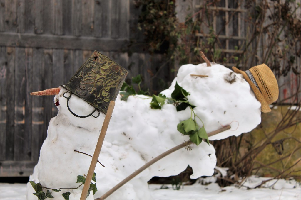 Zwei Schneemänner mit Hüten und Besen